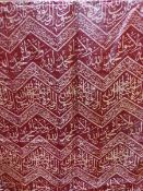 A RED SILK PANEL MACHINE WOVEN IN YELLOW WITH CHEVRON BANDS OF INSCRIPTIONS. 186 x 82cms.