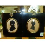 TWO OVAL SILHOUETTES, ONE OF A YOUNG MAN AND THE OTHER OF A CHILD CALLED MARY WITH GILT DETAILING.