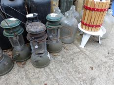 FIVE VINTAGE TILLY LAMPS, TOGETHER WITH A SMALL FRUIT PRESS, SIX LARGE GLASS BOTTLES.