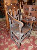 AN EARLY 18th C. OAK ELBOW CHAIR WITH WAVY TOP RAIL ABOVE THE CENTRAL BALUSTER SPLAT, THE SOLID SEAT