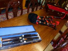 A BOXED SET OF EBONY BAGPIPES, THE BLACK VELVET BAG TRIMMED IN RED, FITTED WITH A CHANTER NAMED