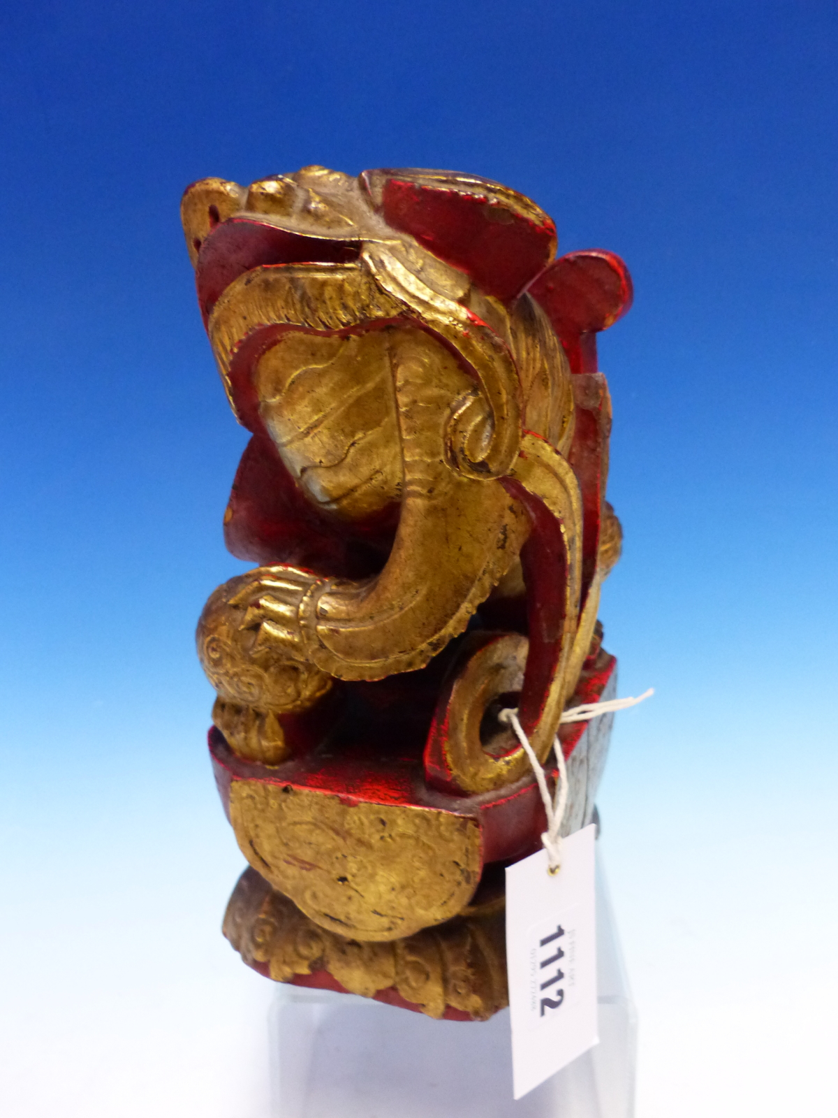A CHINESE CARVED WOOD LION SEATED WITH A BROCADE BALL PARCEL GILT ON A RED LACQUER GROUND. H 23cms. - Image 5 of 5