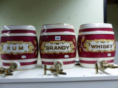 THREE POTTERY SPIRIT BARRELS, EACH WITH BRASS SPIGOTS AND CLARET BANDING ABOUT GILT LABELS,