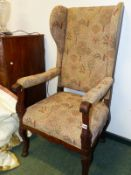 AN ANTIQUE CONTINENTAL OAK WING ARMCHAIR, THE PADDED ARMS WITH FLUTE CARVED HANDLES, THE LEGS CARVED