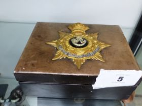 AN OXFORDSHIRE LIGHT INFANTRY GILT AND SILVER BADGE MOUNTED UPON A JEWELLERY BOX.