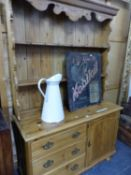 A ANTIQUE PINE DRESSER WITH ENCLOSED TWO SHELF BACK, THE BASE WITH A BANK OF THREE DRAWERS FLANKING