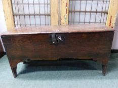 AN EARLY 18th C. OAK PLANK SIDED COFFER, THE NARROW SIDES CARVED WITH AN ARCH TO FORM THE LEGS AND