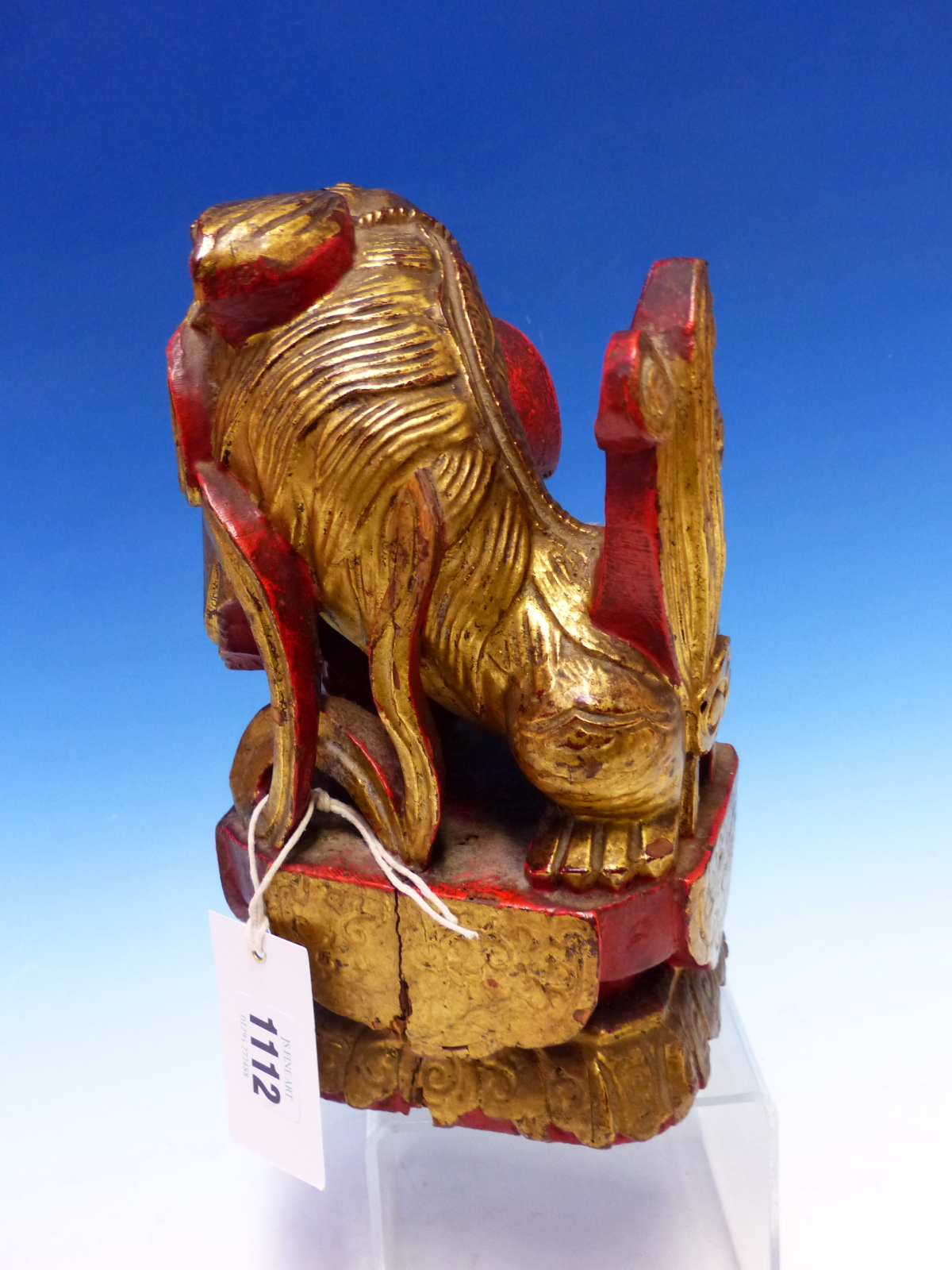 A CHINESE CARVED WOOD LION SEATED WITH A BROCADE BALL PARCEL GILT ON A RED LACQUER GROUND. H 23cms. - Image 4 of 5