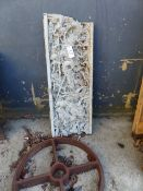AN ORIENTAL DECORATED RELIEF PANEL, TOGETHER WITH A CAST IRON WHEEL.