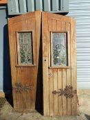 A PAIR OF GOTHIC OAK DOORS WITH FAUX STRAP HINGES AND STAINED GLASS PANELS COMPLETE WITH SURROUND.