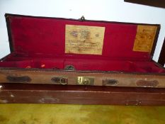 AN ANTIQUE HOLLAND AND HOLLAND GUN CASE AND ANOTHER LATER CASE (2).
