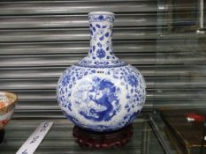 AN ORIENTAL BLUE AND WHITE VASE DECORATED WITH DRAGONS, PHOENIX AND FLOWERS, WITH A WOOD STAND
