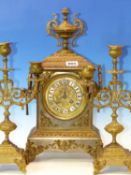 A BRASS CLOCK GARNITURE, THE TWO HANDLED CASE OF THE CLOCK SURMOUNTED BY AN URN, THE MOVEMENT