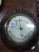AN OAK FRAMED NEGRETTI AND ZAMBRA ANEROID BAROMETER WITH A MERCURY THERMOMETER. Dia. 26cms. TOGETHER