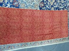 A RED SILK KISWA, MACHINE WOVEN IN GOLDEN YELLOW WITH ISLAMIC INSCRIPTIONS IN AND ABOUT CHEVRON