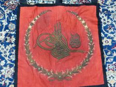 A BLACK CLOTH BACKED AND FRAMED RED SILK BANNER EMBROIDERED IN TWO GOLD COLOURED THREADS WITH A