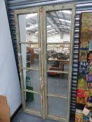 A PAIR OF MIRROR GLAZED PANEL SHUTTER DOORS