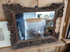 AN ANTIQUE CARVED CHINESE EXPORT FRAME (WITH LOSSES) NOW WITH A MIRROR PLATE OVERALL 50 X 62cms