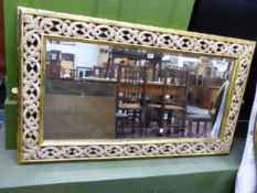 A LARGE MIRROR WITH CARVED PIERCED FRAME.