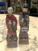 A PAIR OF CHINESE FAMILLE ROSE FIGURES OF A MANDARIN AND HIS WIFE RESPECTIVELY HOLDING A FLY WHISK