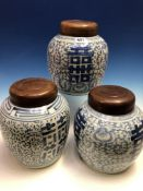 A PAIR OF CHINESE BLUE AND WHITE JARS AND WOOD COVERS PAINTED WITH SHOU CHARACTERS AMONGST SCROLLING