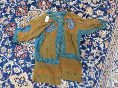AN ISLAMIC TALISMANIC BROWN TUNIC PAINTED WITH BLUE EDGING AND ORANGE DETAILS ABOUT INSCRIPTIONS