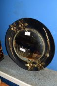 CIRCULAR WALL MIRROR WITH BLACK FRAME AND FLOWERS MODELLED IN RELIEF