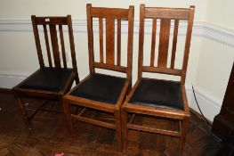 Set of three early 20th century oak, rail back dining chairs with black seats (3)