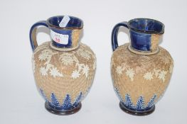 PAIR OF DOULTON LAMBETH EWERS WITH MASK SPOUTS AND APPLIED FLORAL DECORATION ON A GILT GROUND