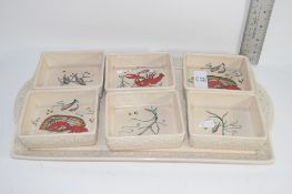 CROWN DEVON SET OF SMALL DISHES ON A LARGER DISH, THE SMALL DISHES DECORATED WITH SEAWEED AND FISH