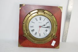 MARINE CLOCK FORMED AS A PORTHOLE MOUNTED ON A MAHOGANY BACK PLATE, APPROX 30CM SQUARE