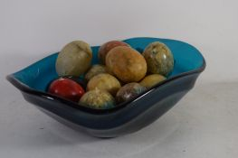 ART GLASS FRUIT BOWL CONTAINING A SELECTION OF STONE EGGS