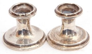 Pair of George V silver dwarf candlesticks of circular shape on stepped spreading loaded bases,