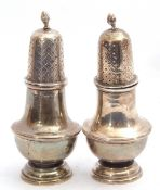 Pair of George V silver peppers having a baluster body, a pierced pull off lid with an urn finial