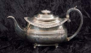 George IV silver tea pot of oval form having a reeded body with applied scroll and shell rim, a