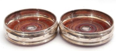 Pair of wine coasters of bellied barrel shape with mahogany turned base, 127mm diam, stamped 925,