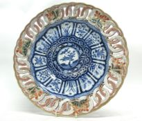 Japanese porcelain large plate with a pierced border, the centre with a floral design in Chinese