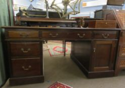 Late 19th/early 20th century mahogany partner's desk with gilt tooled red inset, the two pedestals