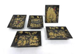 Group of five small Oriental trays with lacquered decoration on a black ground (5)