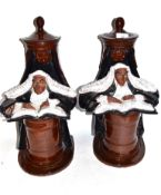Pair of 20th century pottery book ends, the terracotta bodies brown glazed modelled as judges seated