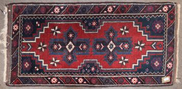 Small 20th century Caucasian wool rug, geometric decoration in red, blue and cream, 130cm x 69cm