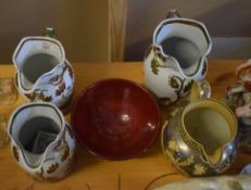 Collection of four Staffordshire jugs with gilt floral design and Prinknash Pottery bowl with red