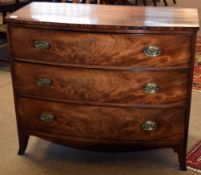 Late Georgian mahogany bow front chest of three drawers with oval embossed brass fittings and raised