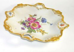 Pair of Continental porcelain dishes decorated in Meissen style of flowers within gilt borders, 30cm
