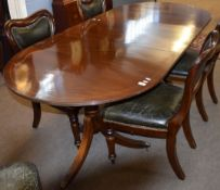 Regency style mahogany twin pedestal dining table, oval shaped, and featuring an inset leaf, top