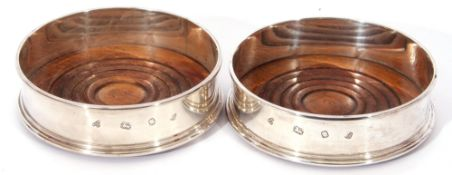 Pair of Elizabeth II silver wine coasters with plain polished sides, turned oak bases with green