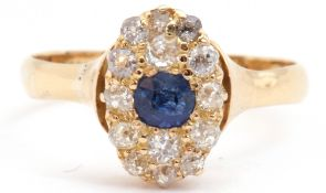 Sapphire and diamond cluster ring, the oval shaped design centring a round cut sapphire and 14 small