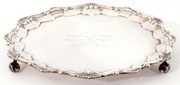 Early 20th century silver salver of shaped circular form on three leaf capped volute-scroll