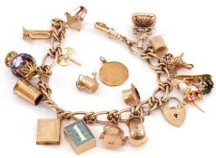 A 9ct gold curb link chain suspending various 9ct gold charms to include enamelled medieval knight