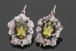 Pair of antique peridot and diamond cluster earrings, each with central oval faceted peridot, 11 x
